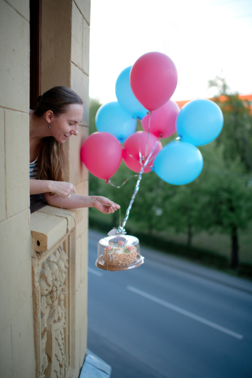 Woman dropping cake from window attached to pink and blue balloons